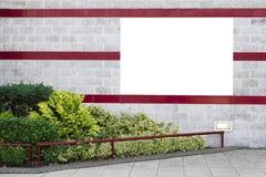 Σαφές άσπρο έμβλημα στο διακοσμητικό τοίχο με τους πράσινους Μπους και τα κόκκινα λωρίδες στοκ φωτογραφία με δικαίωμα ελεύθερης χρήσης