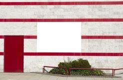 Σαφές άσπρο έμβλημα στο διακοσμητικό τοίχο με τους πράσινους Μπους και τα κόκκινα λωρίδες στοκ φωτογραφία
