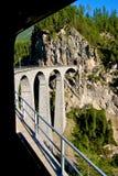 Σαφές, ελβετικό τραίνο Bernina που περνά πέρα από μια οδογέφυρα υψηλή στις Άλπεις στην Ελβετία. Η γραμμή Bernina είναι ο υψηλότερο Στοκ Φωτογραφία