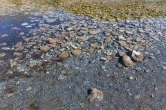 Σαφές νερό με τις πέτρες στο πέρασμα Gemmi στην Ελβετία Στοκ Εικόνα