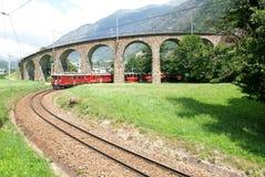 Σαφές τραίνο Bernina σε Brusio στα ελβετικά όρη Στοκ εικόνες με δικαίωμα ελεύθερης χρήσης