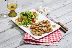 Σαφές cutlet που εξυπηρετείται με τη μικτή σαλάτα και το άσπρο κρασί Στοκ Φωτογραφία