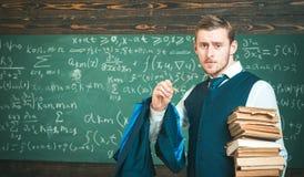 Σαφής εξήγηση Ένδυση και τα γυαλιά δασκάλων η επίσημη φαίνονται έξυπνο, υπόβαθρο πινάκων κιμωλίας Το άτομο στο τέλος του μαθήματο Στοκ Εικόνες
