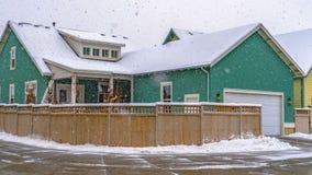 Σαφής χειμερινή άποψη πανοράματος ενός ζωηρόχρωμου σπιτιού με τον ξύλινο φράκτη ενάντια στο νεφελώδη ουρανό στη χαραυγή στοκ εικόνες με δικαίωμα ελεύθερης χρήσης