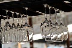 Σαφή γυαλιά κρασιού που κρεμούν στο μετρητή φραγμών στην εικόνα αποθεμάτων οδών πόλεων Στοκ εικόνα με δικαίωμα ελεύθερης χρήσης