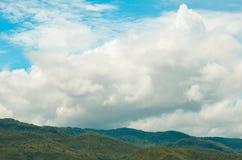 Σαφώς και μουντός ουρανός με τα άσπρα σύννεφα πέρα από τα βουνά στοκ φωτογραφία