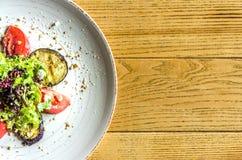 Σαλάτα άνοιξη: ντομάτες, κολοκύθια και χορτάρια, σε ένα άσπρο πιάτο, σε έναν ξύλινο πίνακα στοκ εικόνα