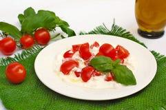 Σαλάτα από τις ντομάτες κερασιών και τυρί εξοχικών σπιτιών με το ελαιόλαδο βασιλικού και Στοκ φωτογραφία με δικαίωμα ελεύθερης χρήσης