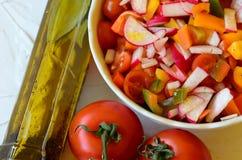 Σαλάτα λαχανικών και το μπουκάλι του ελαίου και των ντοματών ελιών στο άσπρο υπόβαθρο Στοκ εικόνα με δικαίωμα ελεύθερης χρήσης