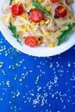 Σαλάτα ζυμαρικών με το κεράσι, τον τόνο, το καλαμπόκι και το arugula ντοματών στο μπλε ξύλινο υπόβαθρο Τοπ όψη Στοκ Φωτογραφίες