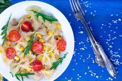 Σαλάτα ζυμαρικών με το κεράσι, τον τόνο, το καλαμπόκι και το arugula ντοματών στο μπλε ξύλινο υπόβαθρο Τοπ όψη Στοκ Εικόνες