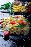 Σαλάτα ζυμαρικών στο πιάτο πλακών με το κεράσι, τον τόνο, το καλαμπόκι και το arugula ντοματών Συστατικά μαγειρεύοντας συστατικά  Στοκ εικόνες με δικαίωμα ελεύθερης χρήσης