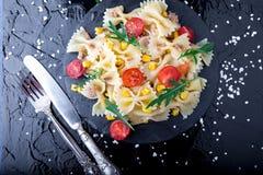 Σαλάτα ζυμαρικών στο πιάτο πλακών με το κεράσι, τον τόνο, το καλαμπόκι και το arugula ντοματών κοντά στο μαχαίρι και το κουτάλι Τ Στοκ Εικόνες