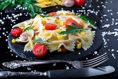 Σαλάτα ζυμαρικών στο πιάτο πλακών με το κεράσι, τον τόνο, το καλαμπόκι και το arugula ντοματών Συστατικά μαγειρεύοντας συστατικά  Στοκ Εικόνα