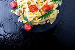 Σαλάτα ζυμαρικών στο πιάτο πλακών με το κεράσι, τον τόνο, το καλαμπόκι και το arugula ντοματών Τοπ όψη μαγειρεύοντας συστατικά ιτ Στοκ Φωτογραφίες