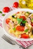 Σαλάτα ζυμαρικών Fusilli με τον τόνο, τις ντομάτες, τις μαύρους ελιές και το βασιλικό στο γκρίζο υπόβαθρο πετρών Στοκ Εικόνα