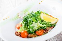 Σαλάτα θαλασσινών με τα μύδια, τα καλαμάρια, τις ντομάτες χταποδιών, arugula, μαρουλιού και κερασιών στο ξύλινο υπόβαθρο Στοκ φωτογραφίες με δικαίωμα ελεύθερης χρήσης
