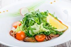 Σαλάτα θαλασσινών με τα μύδια, τα καλαμάρια, τις ντομάτες χταποδιών, arugula, μαρουλιού και κερασιών στο ξύλινο υπόβαθρο Στοκ Εικόνες