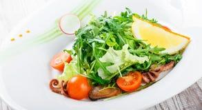 Σαλάτα θαλασσινών με τα μύδια, τα καλαμάρια, τις ντομάτες χταποδιών, arugula, μαρουλιού και κερασιών στο ξύλινο υπόβαθρο Στοκ φωτογραφία με δικαίωμα ελεύθερης χρήσης