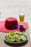 Σαλάτα θαλασσινών, πορτοκαλής φρέσκος χυμός, καπέλο και γυαλιά ηλίου στον πίνακα κοντά στη θάλασσα Στοκ φωτογραφία με δικαίωμα ελεύθερης χρήσης