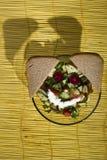 Σαλάτα και ψωμί σε ένα κίτρινο χαλί μπαμπού στο ξύλινο υπόβαθρο Στοκ Εικόνες