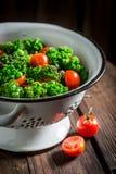 Σαλάτα κατσαρού λάχανου άνοιξη με τα πράσινα μπιζέλια και τις ντομάτες κερασιών Στοκ Εικόνες
