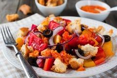 Σαλάτα με τα πιπέρια, τις ντομάτες, τα κρεμμύδια, τις ελιές και croutons με το παλαιό ξύλινο υπόβαθρο sousomna Στοκ Εικόνα