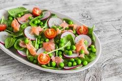 Σαλάτα με τα πράσινα μπιζέλια, το ραδίκι, τις ντομάτες κερασιών και το σπανάκι σε ένα ωοειδές κεραμικό πιάτο στον ελαφρύ ξύλινο π Στοκ φωτογραφίες με δικαίωμα ελεύθερης χρήσης
