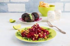 Σαλάτα με τα ψημένα τεύτλα, το arugula, τις σταφίδες και τα ξύλα καρυδιάς σε ένα πράσινο πιάτο στον πίνακα στην κουζίνα Στοκ φωτογραφίες με δικαίωμα ελεύθερης χρήσης