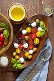Σαλάτα με τις χρωματισμένες ντομάτες, μικρή μοτσαρέλα, πράσινο olivesand β Στοκ Φωτογραφία