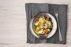 Σαλάτα με το αβοκάντο και γαρίδες στο παλαιό μεταλλικό πιάτο με το εκλεκτής ποιότητας δίκρανο Στοκ εικόνα με δικαίωμα ελεύθερης χρήσης