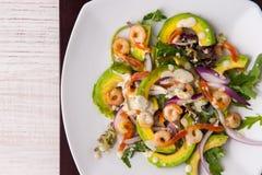 Σαλάτα με το αβοκάντο, το arugula και τις γαρίδες στην άσπρη τετραγωνική τοπ άποψη πιάτων Στοκ εικόνα με δικαίωμα ελεύθερης χρήσης