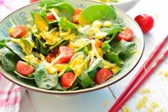 Σαλάτα με το σπανάκι, τα κρεμμύδια, τις ντομάτες και μια κίτρινη turmeric σάλτσα Στοκ Φωτογραφία
