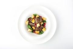 Σαλάτα με το συκώτι κοτόπουλου και σπανάκι κατά την άσπρη τοπ άποψη πιάτων Στοκ φωτογραφία με δικαίωμα ελεύθερης χρήσης