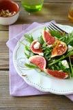 Σαλάτα με το arugula, τα σύκα και το τυρί στο άσπρο πιάτο Στοκ εικόνα με δικαίωμα ελεύθερης χρήσης
