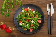 Σαλάτα με το arugula, φράουλες, τυρί εξοχικών σπιτιών, ελαιόλαδο, σε ένα μαύρο πιάτο, ξύλινο υπόβαθρο Κινηματογράφηση σε πρώτο πλ Στοκ Φωτογραφία
