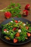 Σαλάτα με το arugula, φράουλες, τυρί εξοχικών σπιτιών, ελαιόλαδο, σε ένα μαύρο πιάτο, ξύλινο υπόβαθρο Κινηματογράφηση σε πρώτο πλ Στοκ Εικόνα
