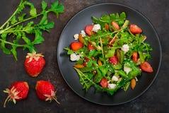 Σαλάτα με το arugula, φράουλες, τυρί εξοχικών σπιτιών, ελαιόλαδο, σε ένα μαύρο πιάτο, παλαιό μαύρο υπόβαθρο Κινηματογράφηση σε πρ Στοκ φωτογραφίες με δικαίωμα ελεύθερης χρήσης