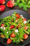 Σαλάτα με το arugula, φράουλες, τυρί εξοχικών σπιτιών, ελαιόλαδο, σε ένα μαύρο πιάτο, παλαιό μαύρο υπόβαθρο Κινηματογράφηση σε πρ Στοκ Φωτογραφίες