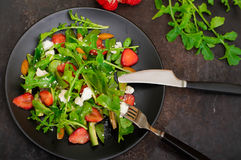 Σαλάτα με το arugula, φράουλες, τυρί εξοχικών σπιτιών, ελαιόλαδο, σε ένα μαύρο πιάτο, παλαιό μαύρο υπόβαθρο Κινηματογράφηση σε πρ Στοκ φωτογραφία με δικαίωμα ελεύθερης χρήσης