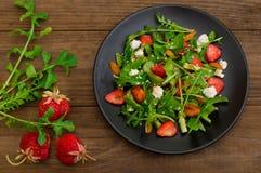 Σαλάτα με το arugula, φράουλες, τυρί εξοχικών σπιτιών, ελαιόλαδο, σε ένα μαύρο πιάτο, ξύλινο υπόβαθρο Κινηματογράφηση σε πρώτο πλ Στοκ Φωτογραφίες