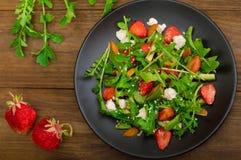 Σαλάτα με το arugula, φράουλες, τυρί εξοχικών σπιτιών, ελαιόλαδο, σε ένα μαύρο πιάτο, ξύλινο υπόβαθρο Κινηματογράφηση σε πρώτο πλ Στοκ φωτογραφίες με δικαίωμα ελεύθερης χρήσης