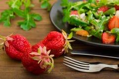 Σαλάτα με το arugula, φράουλες, τυρί εξοχικών σπιτιών, ελαιόλαδο, σε ένα μαύρο πιάτο, ξύλινο υπόβαθρο Κινηματογράφηση σε πρώτο πλ Στοκ φωτογραφία με δικαίωμα ελεύθερης χρήσης