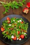Σαλάτα με το arugula, φράουλες, τυρί εξοχικών σπιτιών, ελαιόλαδο, σε ένα μαύρο πιάτο, ξύλινο υπόβαθρο Κινηματογράφηση σε πρώτο πλ Στοκ Εικόνες