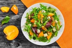 Σαλάτα με persimmon τις φέτες, μίγμα των φύλλων μαρουλιού, μπλε τυρί Στοκ φωτογραφία με δικαίωμα ελεύθερης χρήσης