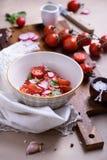Σαλάτα ντοματών κινηματογραφήσεων σε πρώτο πλάνο με τα ζωηρόχρωμα εύγευστα συστατικά στο υπόβαθρο Βιο υγιή τρόφιμα, χορτάρια και  Στοκ Εικόνα