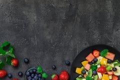 Σαλάτα νωπών καρπών στο σκοτεινό υπόβαθρο Τοπ άποψη, διάστημα αντιγράφων Στοκ εικόνες με δικαίωμα ελεύθερης χρήσης