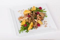 Σαλάτα παπιών κοτόπουλου με το arugula, σμέουρα, πατάτες, σπόροι ηλίανθων σε ένα τετραγωνικό άσπρο υπόβαθρο πιάτων Στοκ Εικόνες