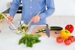 Σαλάτα στο κύπελλο γυαλιού που γίνεται από το αρσενικό στην κουζίνα Στοκ Εικόνες