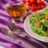Σαλάτα του arugula και των ντοματών με το έλαιο και τα χορτάρια Στοκ εικόνα με δικαίωμα ελεύθερης χρήσης
